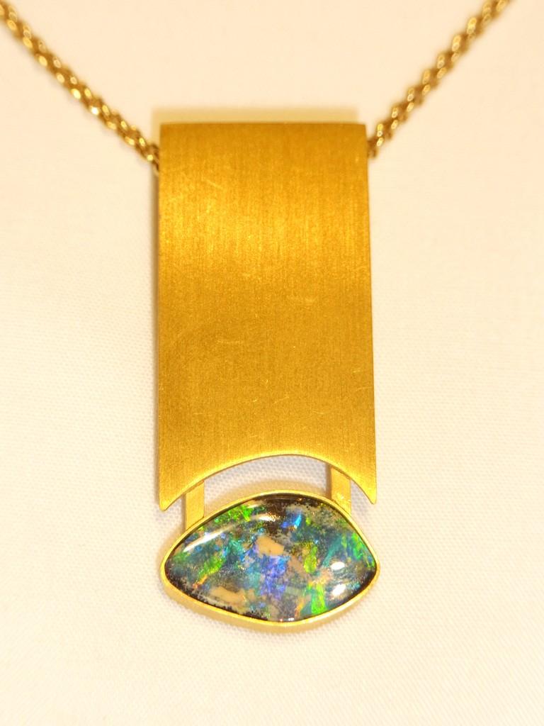 Opal mit großem, flächigen Goldobjekt als Anhänger.
