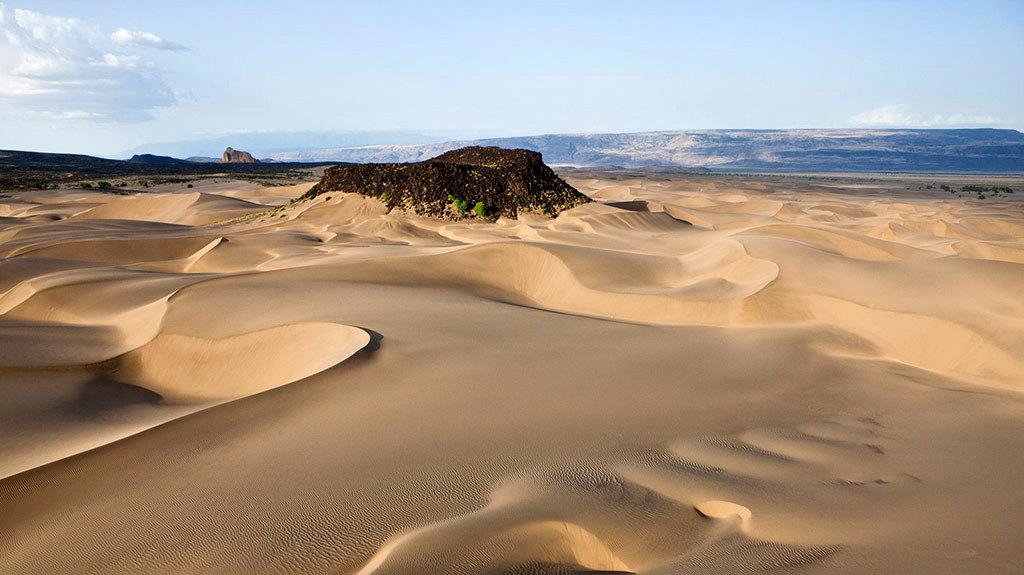 Kenya-Suguta Valley. Dune con Aruba Rock visibile sullo sfondo. Qui le temperature raggiungono i 71°C.