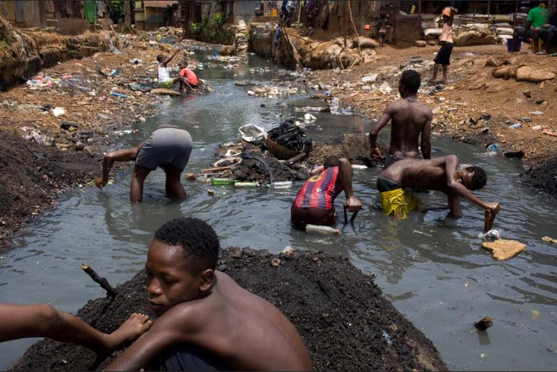 Ragazzi cercano qualsiasi cosa di valore nel fiume Crocodile nello slum di Kroo Bay a Freetown, in Sierra Leone