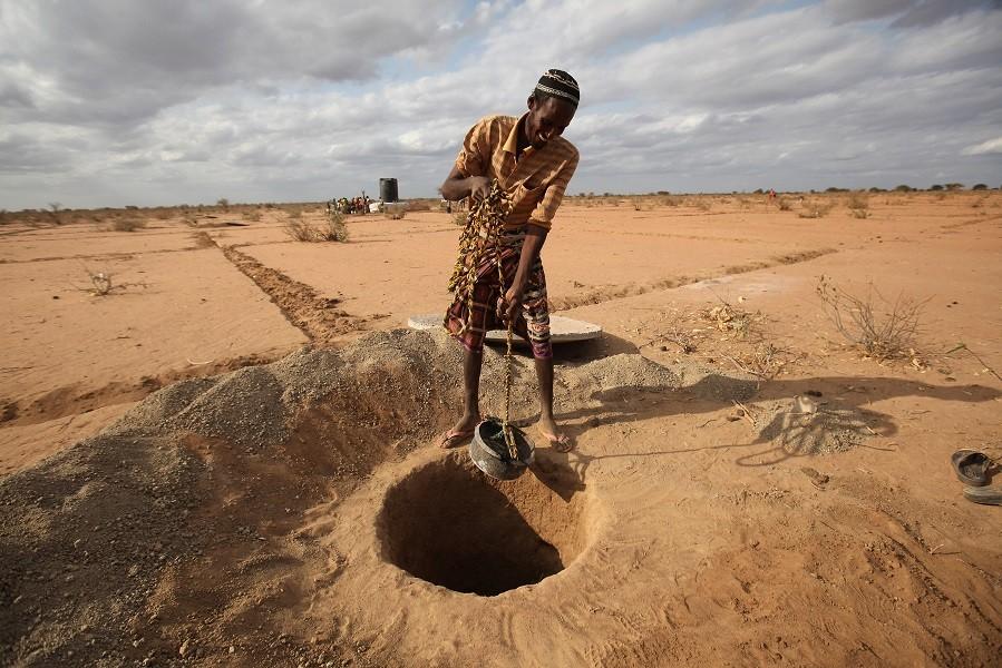 Un uomo cerca dell'acqua in un pozzo. Dadaab, Kenya