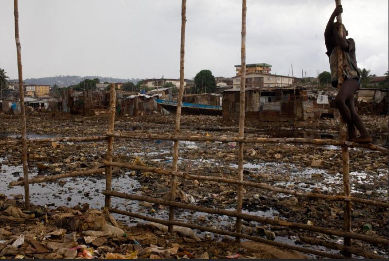 Un bambino vicino a pericolose acque di scolo insieme a zanzare e vermi parassiti nello slum di Kroo Bay a Freetown, in Sierra Leone