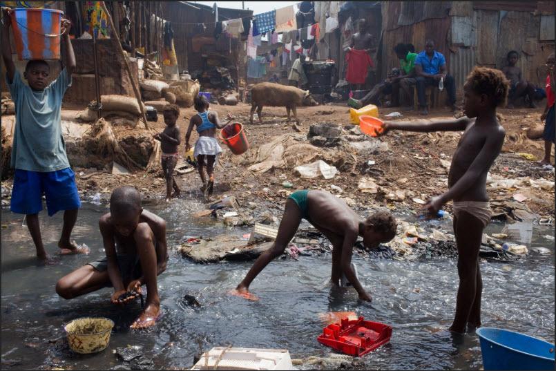 Bambini recuperano qualsiasi cosa di valore dal fiume Crocodile nello slum di Kroo Bay a Freetown, in Sierra Leone
