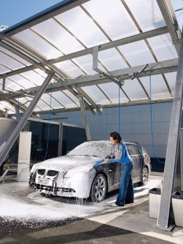 Frau beim Einschäumen Ihres Wagens in einer SB-Waschbox von Wash Clean Bochum