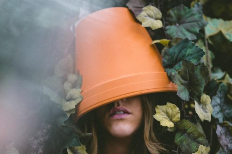 Femme avec pot de fleur sur la tête