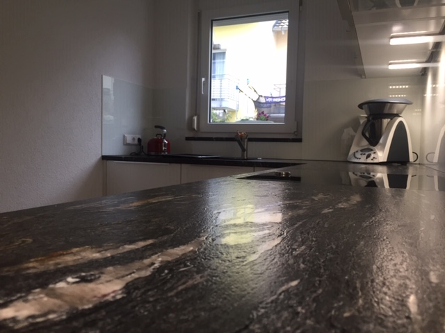 Hochglanz-Weiß Küche mit Neff Geräten und Natursteinarbeitsplatte von CS Baupartner