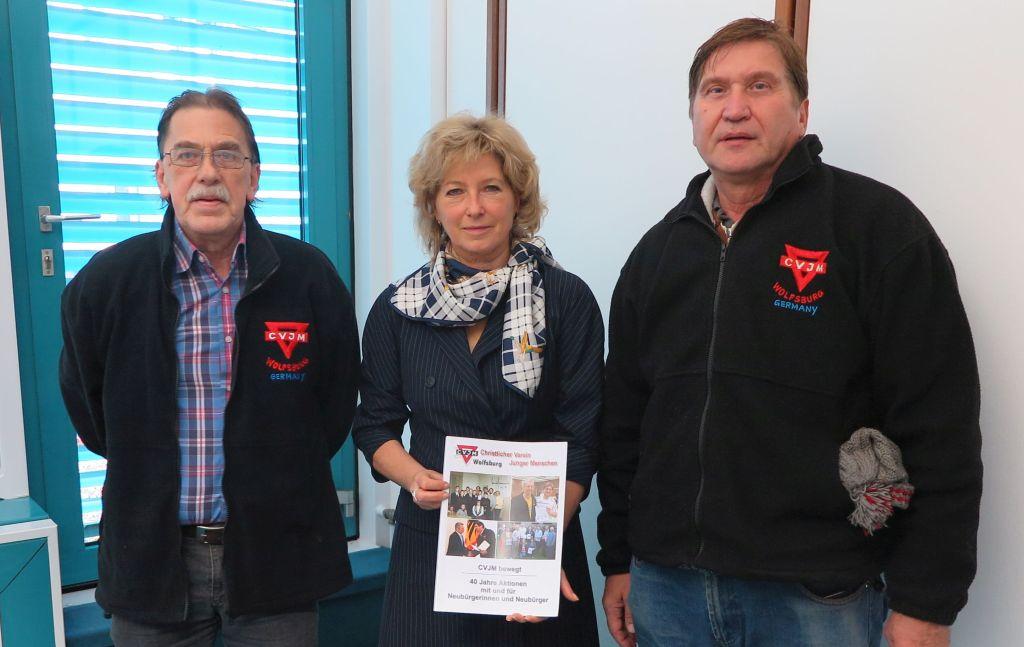 Claudia Kayser (mit Buch) von der Volksbank Brawo mit Ferdinand Uecker (links) und Manfred Wille