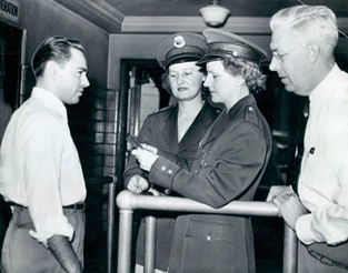 Detrioit, Michigan 1944 Ann Stankun and Louise Boer, the first women to serve as immigrant inspectors at the port of Detroit, are closely monitored by their supervisor during passport review.