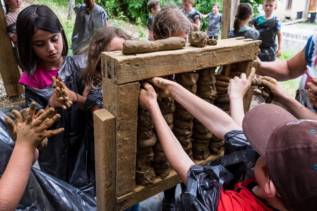 Les petites mains enlacent les colombins de torchis autour des palençons