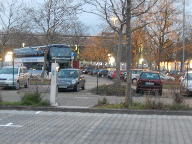 Gegenüber ein großer Parkplatz, dahinter das alte Stadion.