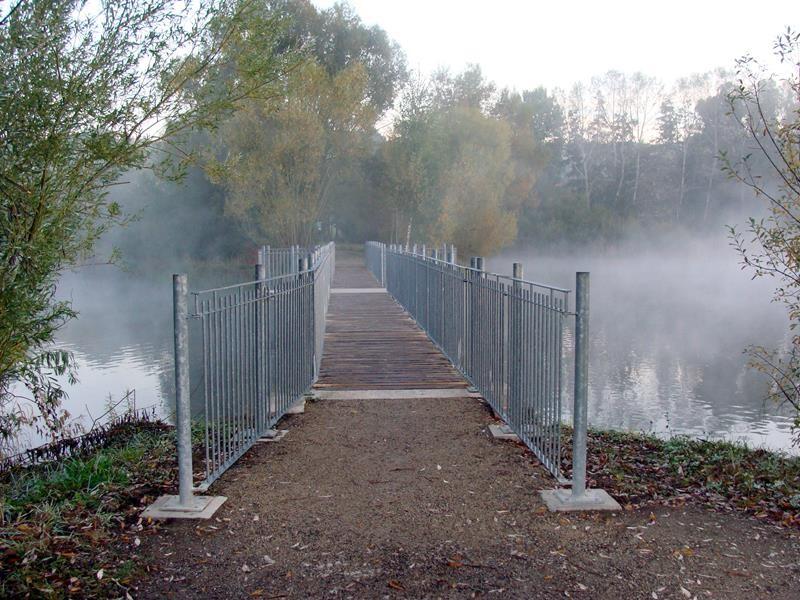 Über die Brücke führt der Weg weiter um den See herum.