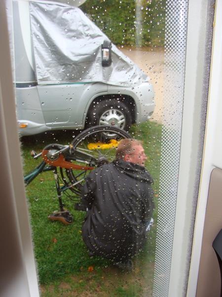 Mein Fahrrad hat einen Platten....da haben die Männer was zu tun. Im Regen unter der Markise wird das Loch geflickt.
