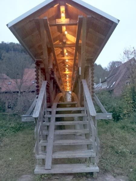Toll beleuchtet Brücke, die über einen Bach führt zu Wohnhäusern.