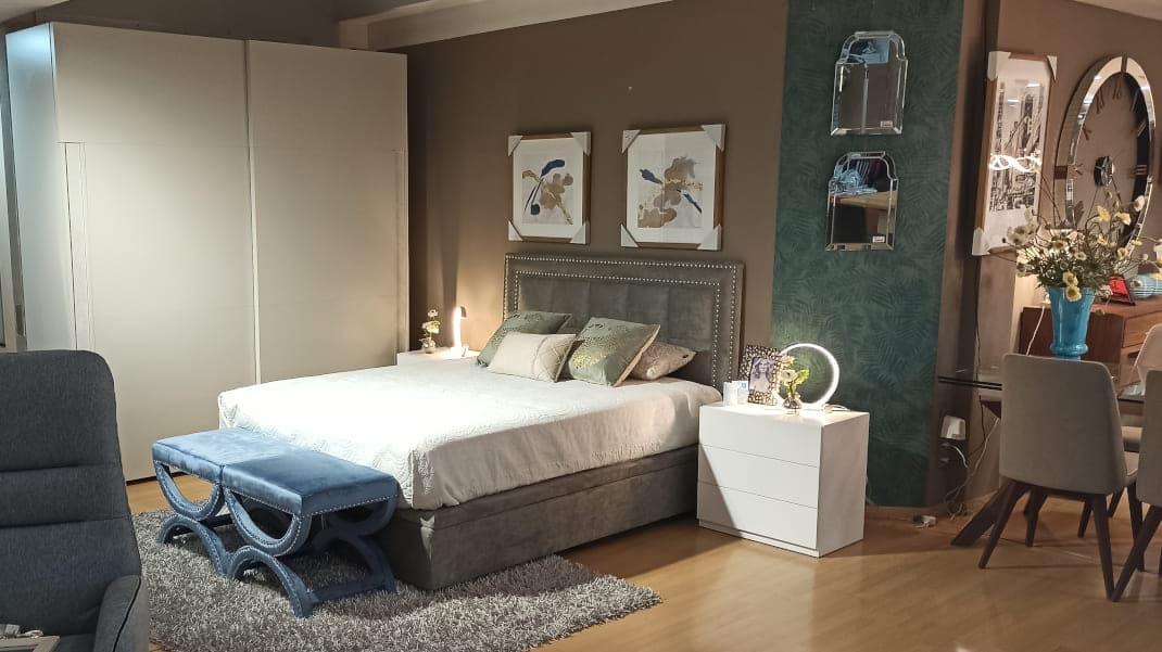 dormitorio con armario, cabezal, cama, mesita de noche, cuadros, banqueta, lamparas de mesa y espejos pequeños.
