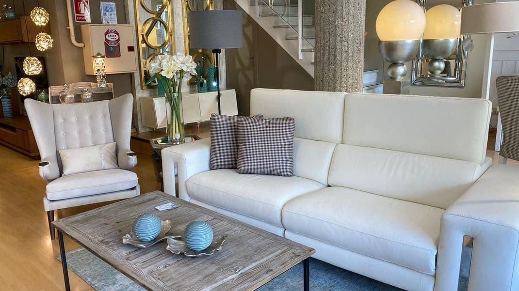 sofá de piel, sillón grande, lamparas, mesa de centro y espejos.