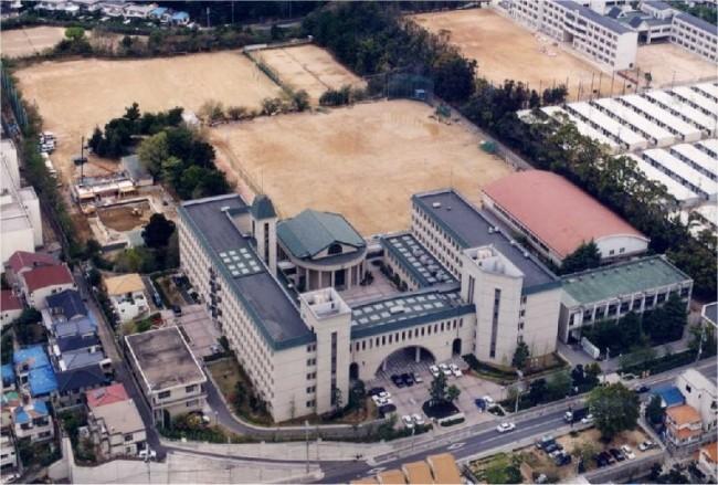 新校舎の全景、1995(平成7)年4月に撮影したものです。  阪神淡路大震災の傷跡が、屋根の青いビニールシートや画面右側の旧商大跡地の仮設住宅に見られます。