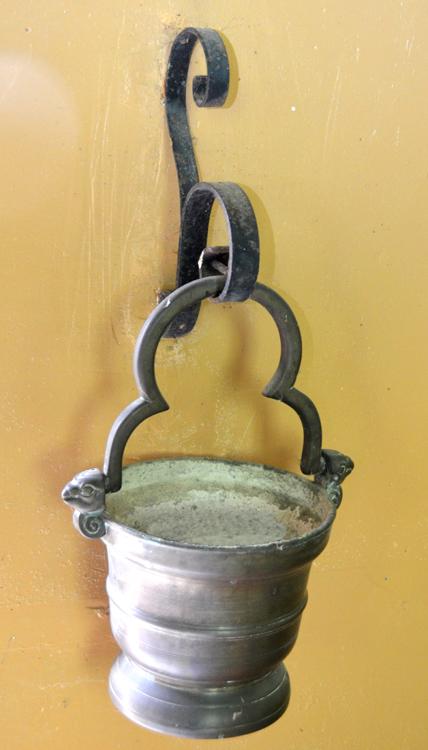 A l'entrée de l'église de Dargnies: un seau à eau bénite en guise de bénitier