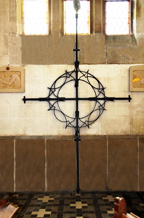 La croix du clocher, qui menaçait de s'effondrer, est maintenant protégée à l'intérieur de l'église