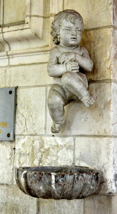 Bénitier insolite dans l'église de Cerisy- Que fait cet enfant au-dessus du bénitier?