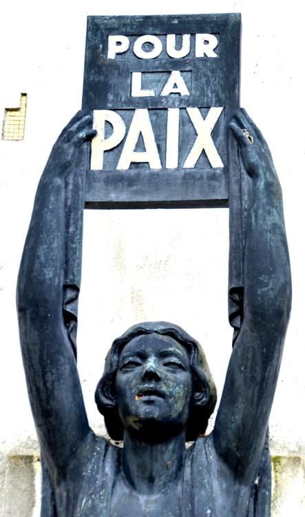 """Gros plan sur le monument aux morts: L'institutrice brandit le panneau: """"Pour la Paix"""""""