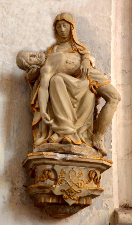 Sur le socle de la statue de cette belle Vierge de Pitié, les initiales du donateur