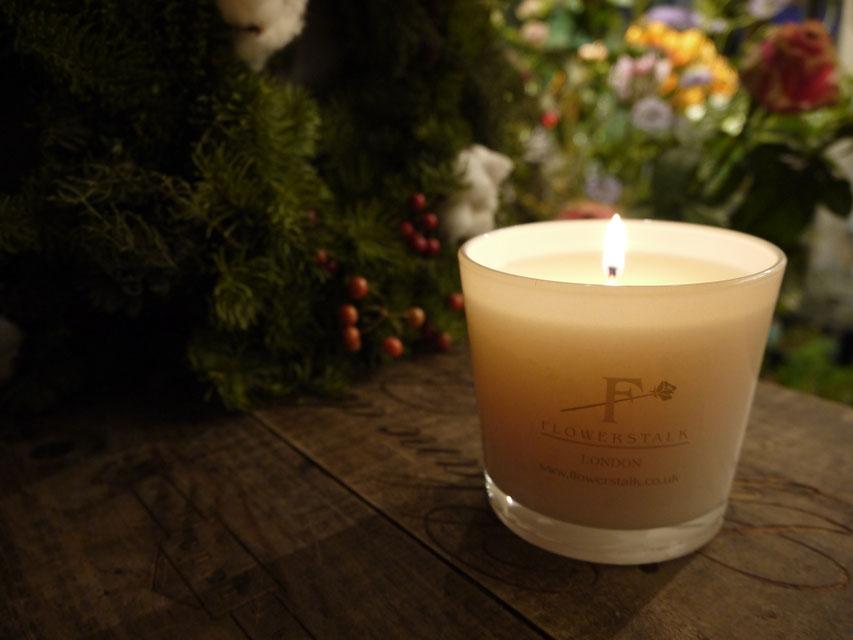 フラワーストークキャンドル・パチョリ香草 スパイシーでエキゾチックな香りは心を落ち着かせる瞑想の時間を演出する。明かりを落とした花屋の店内で背景には花をセットし一眼レフにて撮影。