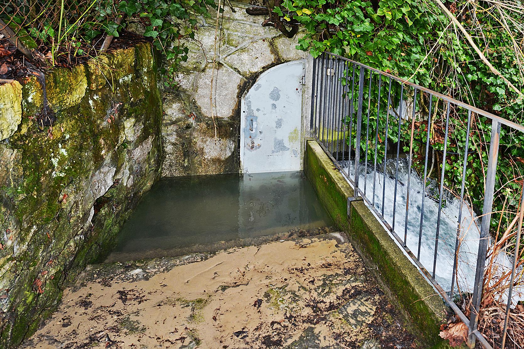 Eingang zur Quellfassung. Die Eingangstüre ist vom Wasser überschwemmt