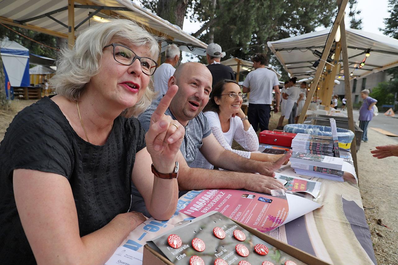 """An einem der Stände verkaufen Sylvia Scalabrino, David Friedmann und Assunta Ginanneschi den 1.-August-Pin und das """"Gundeli-Buch""""."""
