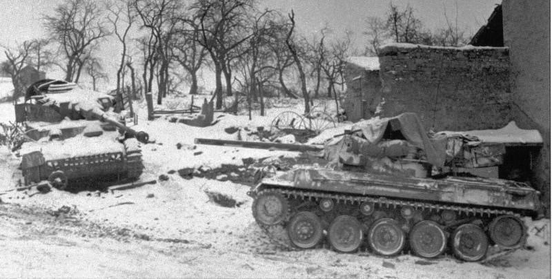 Ce M18 dépasse un Pz IV détruit durant la bataille des Ardennes, où ce sont illustrés les Hellcat
