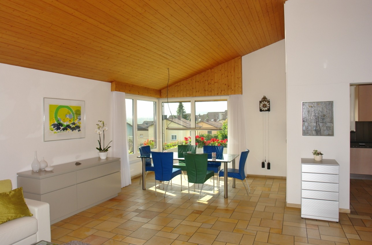 Blick vom Wohn- hin zum Essbereich: Übergrosse, bis zur Dachuntersicht reichende Raumhöhe