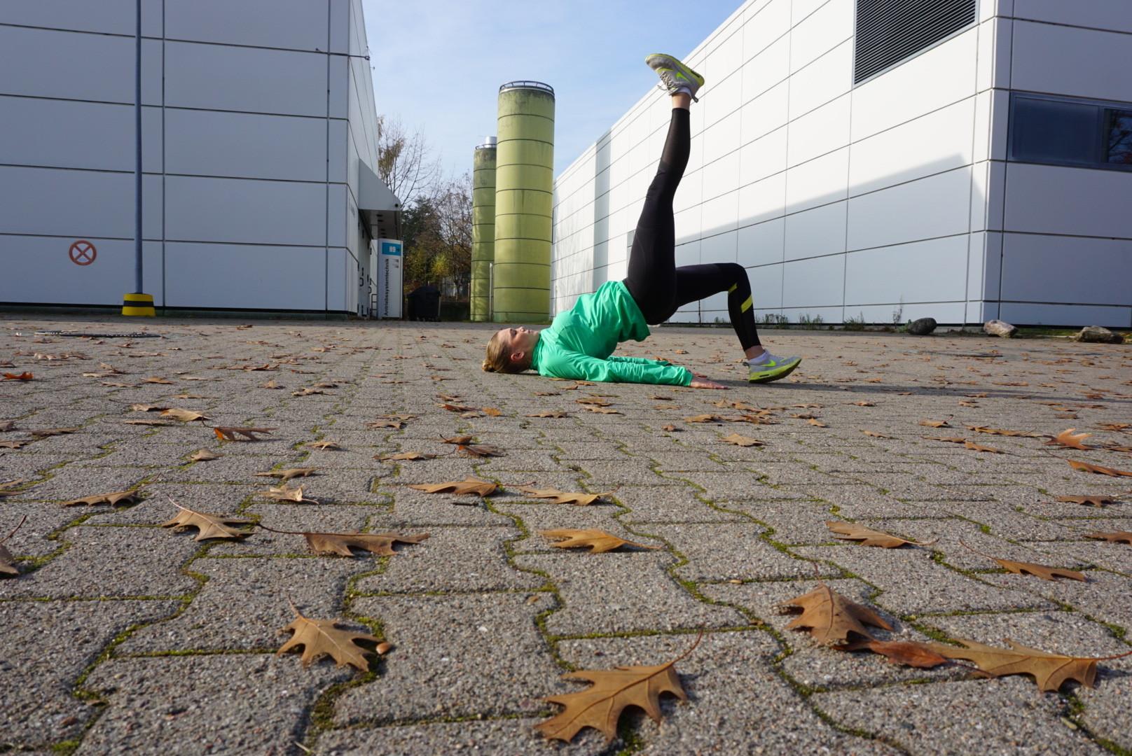 Einbeiniges Hüftheben für einen knackigen Popo. Dazu auf den Boden legen, die Arme liegen flach neben dem Körper. Ein Bein ausstrecken. Dann die Hüfte nach oben heben und wieder absenken. Das Gewicht ist auf der Ferse.