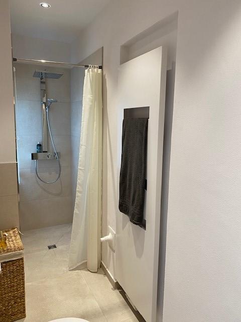 In eine Niesche wurde ein formschöner Handtuchheizkörper installiert.