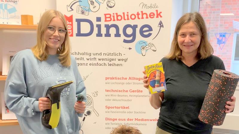 Noelle Griesbach (Auszubildende) und Sabine Treuten (v.l.) präsentieren die Mobile Bibliothek der Dinge in der Stadtbücherei.