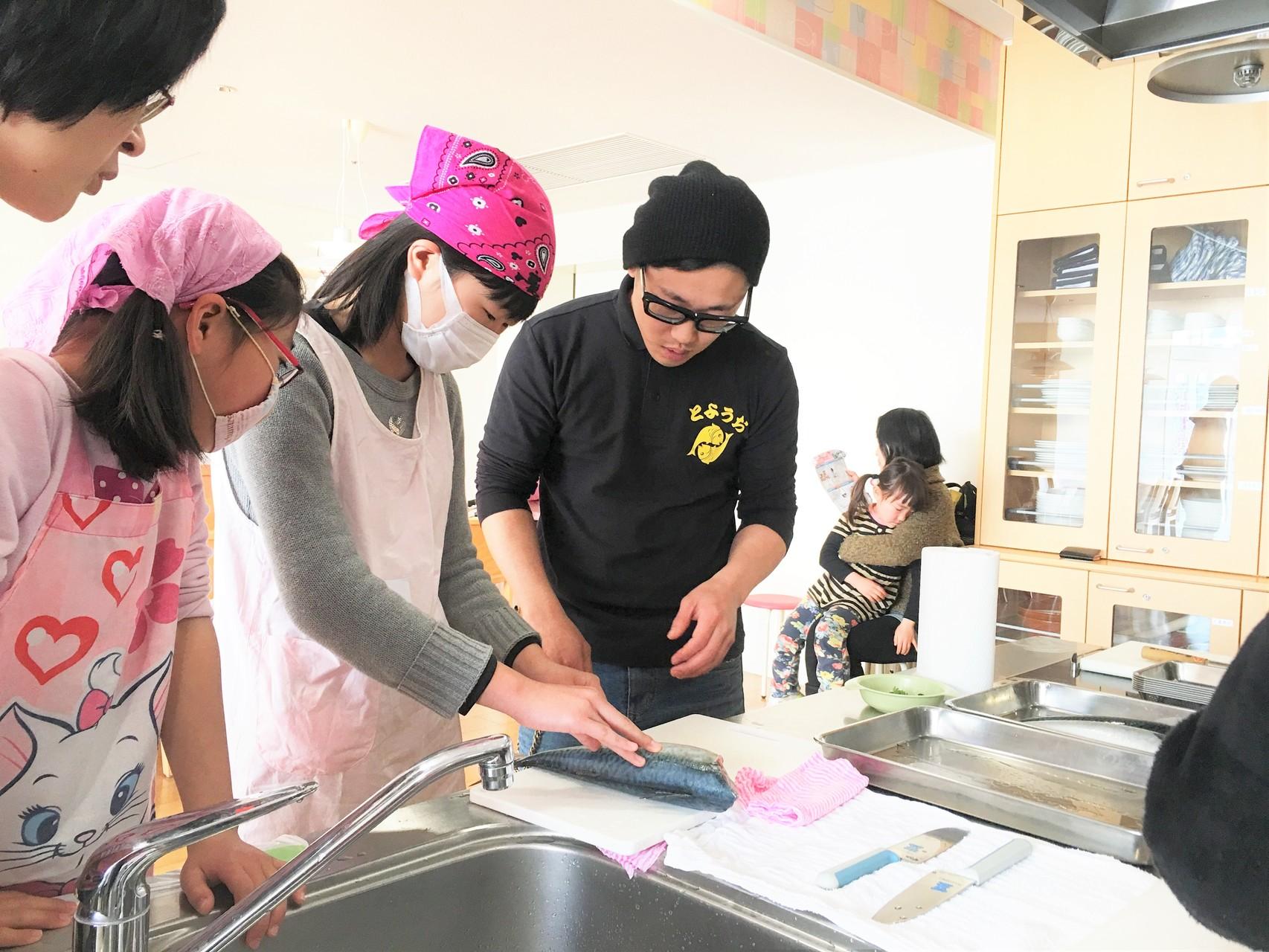 魚市場鮮魚部の山本尚さん(右端)の指導を受ける生徒。