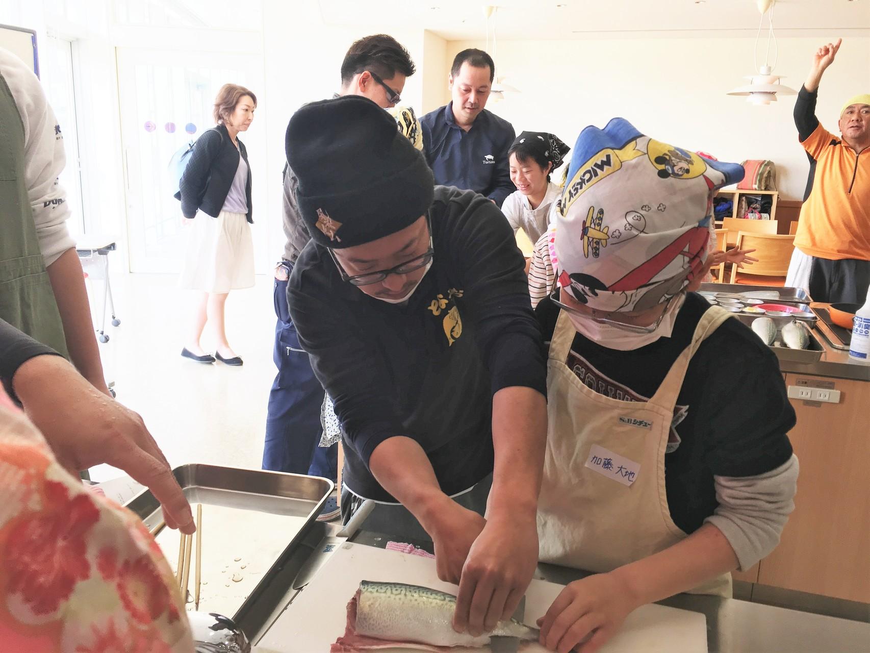 魚市場鮮魚部の山本洋さん(左端)の指導を受ける生徒。