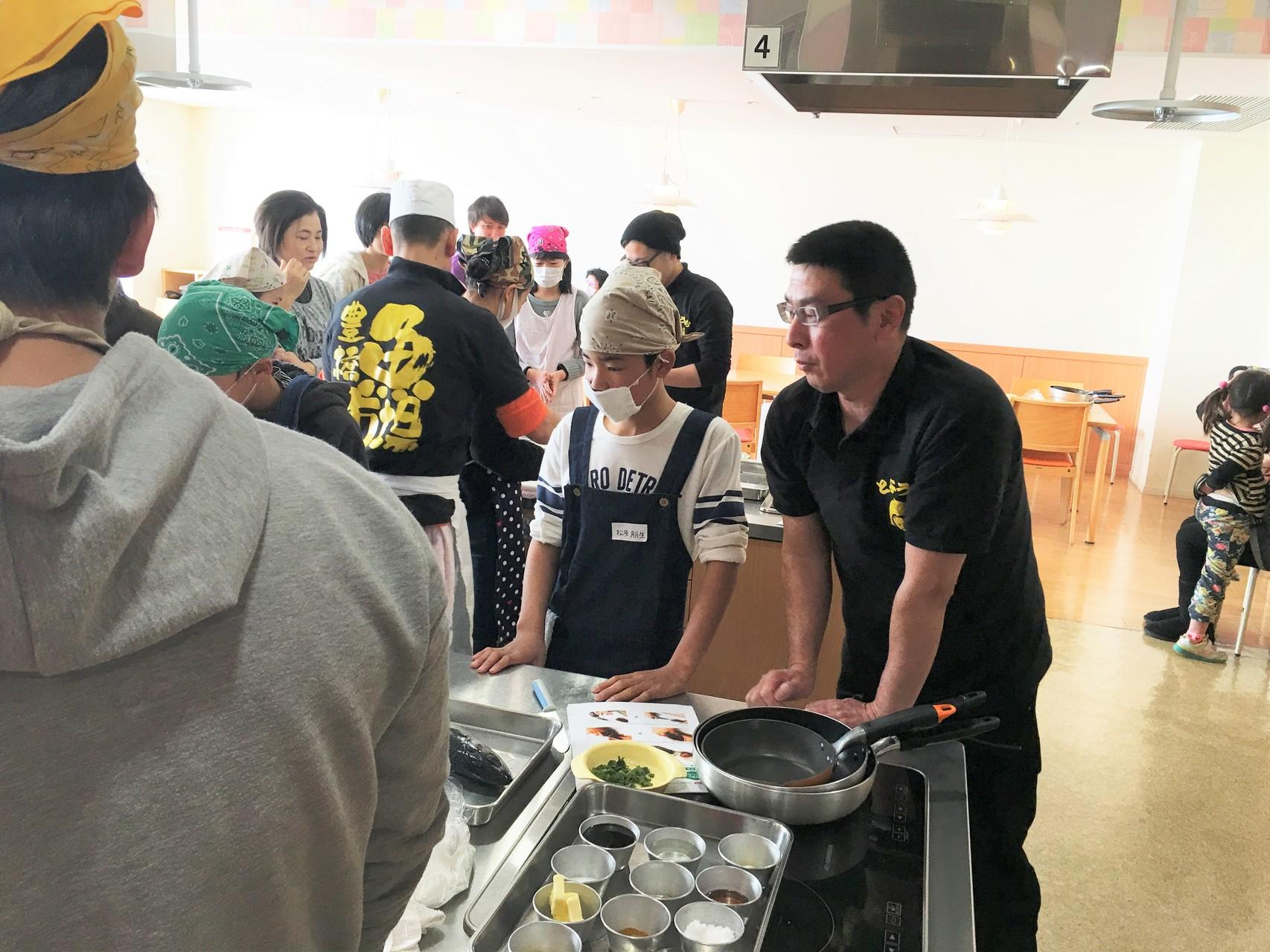 魚市場鮮魚部の富山さん(右端)の指導を受ける生徒。