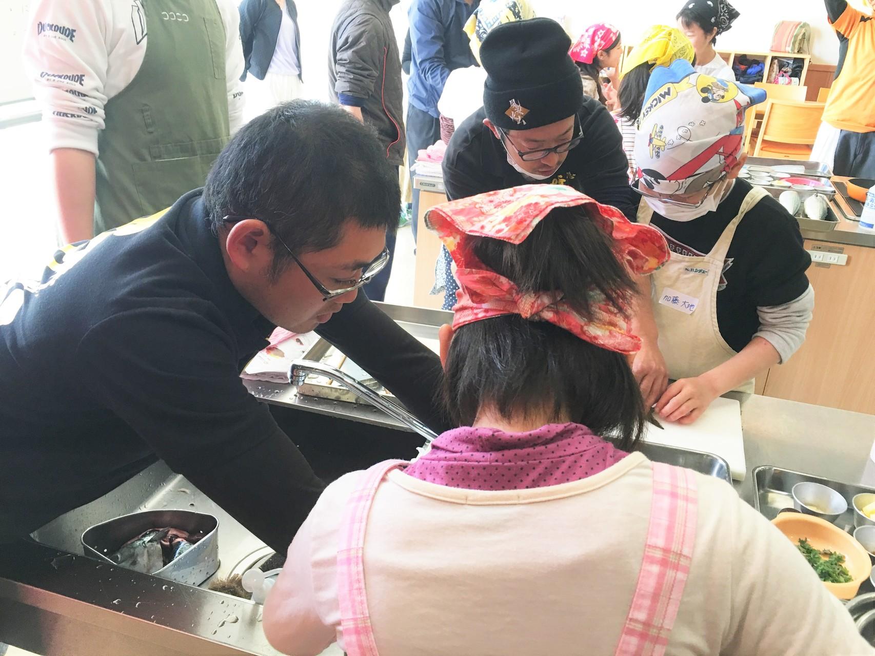 魚市場塩干部の牧野さん(左端)の指導を受ける生徒。