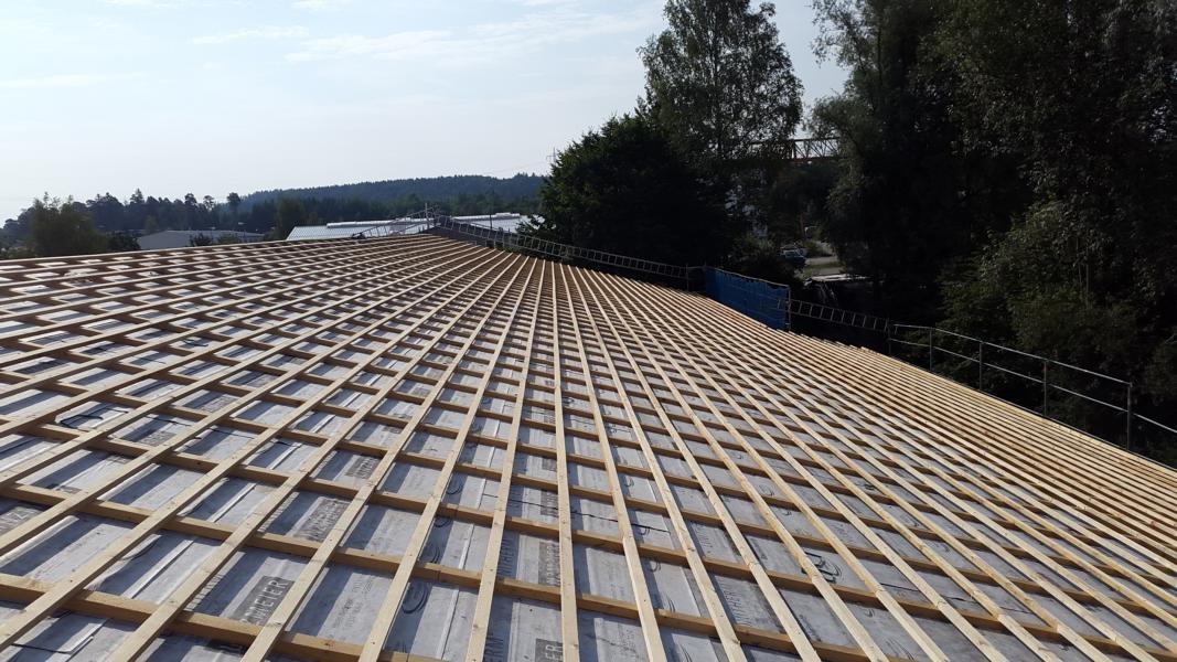 Komplett aufgestellter Dachstuhl mit Lattung und Dämmung
