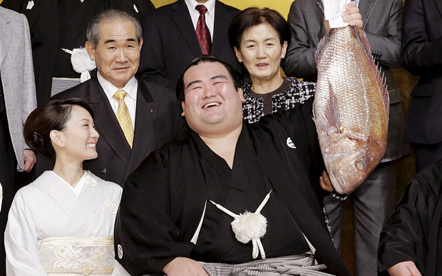 Sumo-wrestler Ozeki-Kotoshogiku holds up a sea bream as he celebrates his victory (01.2016)