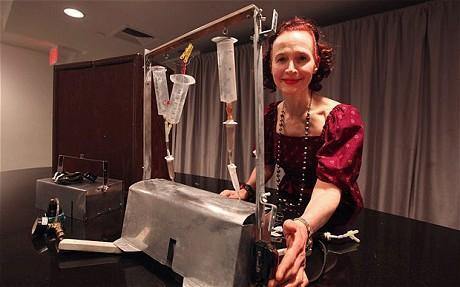 ジャック・ケヴォーキアン博士の姪であるエヴァ・ヤヌスが「死の機械」と呼ばれる「タナトロン」と一緒に笑顔で写真を撮影している。