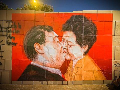 キャリー・ラムと習近平のカリカチュア。ベルリンの壁に描かれたグラフィティ『神よ、この死に至る愛の中で我を生き延びさせ給え』とよく似ている。
