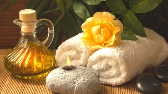 Kerze, Handtücher, Blume und Öl als Wellnessarrangement