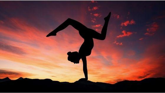 Frau im Handstand vor Sonnenuntergang