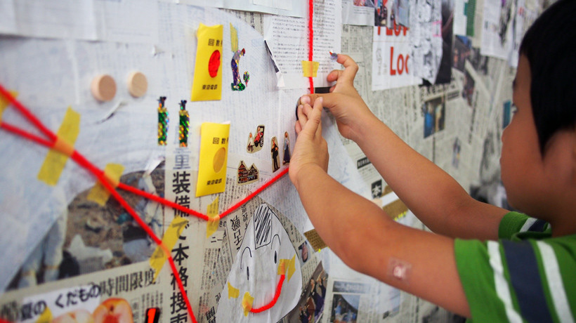 震災を伝える新聞の上に、子どもたちの作品が作られていく。変えることのできない過去の上に、「今」が上書きされていく。