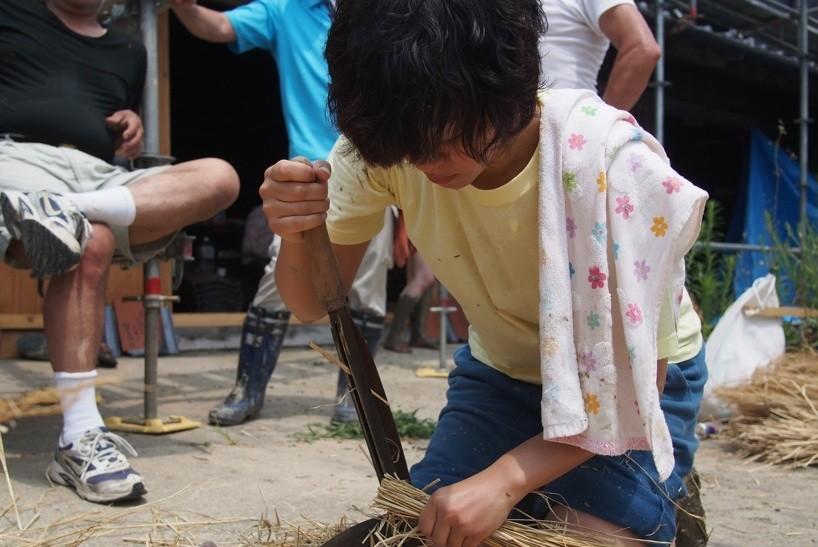 泥に混ぜ込む藁も、参加者が職人に手ほどきをうけながらつくっていく。