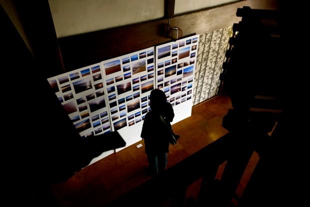 永崎海岸の朝焼けを撮り続けた作品に見入る観覧者。大型作品も数点展示されている。