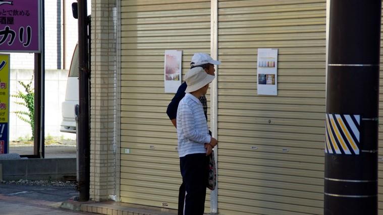 あさんぷぉの写真は通りのシャッターに展示された。まちゆく人たちも足をとめる。photo by monaken