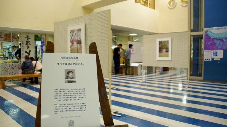 大森克己写真展「すべては初めて起こる」。大森の写真の脇では、手づくり豆腐店が通常営業していた。photo by monaken