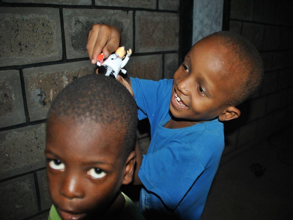 """Spassvogel Isaac """"rasiert"""" Caleb die Haare mit einem Spielzeug."""