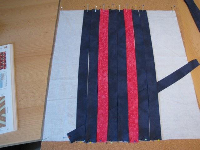 """Die vertikalen Streifen werden auf die Korkplatte auf einen """"Trägerstoff"""", der am Schluß hinter dem Geflochtenen verbleibt, festgesteckt. Den ersten """"Querstreifen"""" im 30-Grad-Winkel zu den vertikalen Streifen einflechten."""