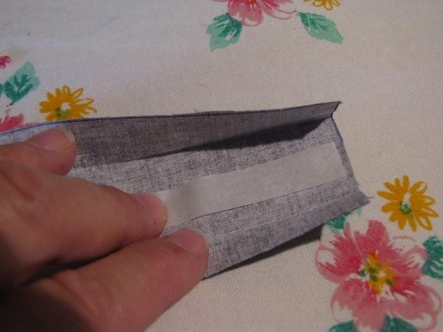 Vlisofix mit der rauhen Seite auf die linke Seite des Stoffes legen, Schrägband zuklappen und mit Stufe 2 langsam bügeln